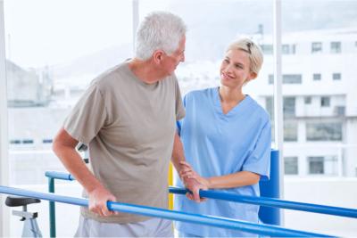 nurse helping an elderly man to walk