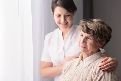 smiling caregiver looking at the elderly woman