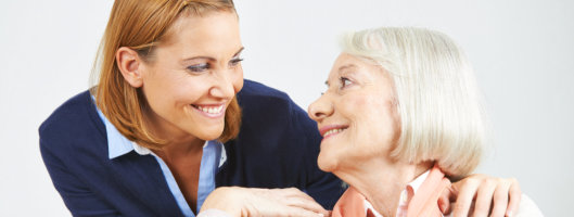 caregiver and elderly woman smiling at each other